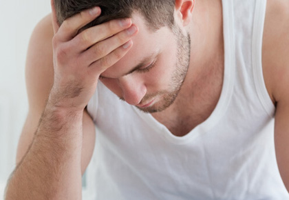 Man suffering from headache with hands on forehead