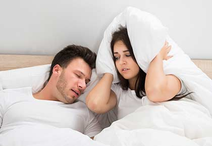 Man snoring while his wife is covering ears with the pillow